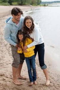 Familj som promenerar vid stranden